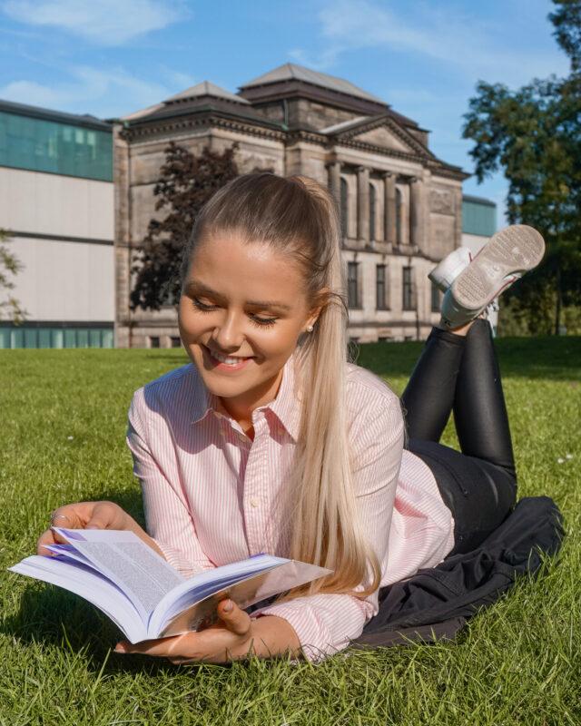 Celine Nadolny - Frau liegt in Wiese und liest Buch