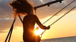Glücklich leben: Frau schaukelt bei Sonnenuntergang